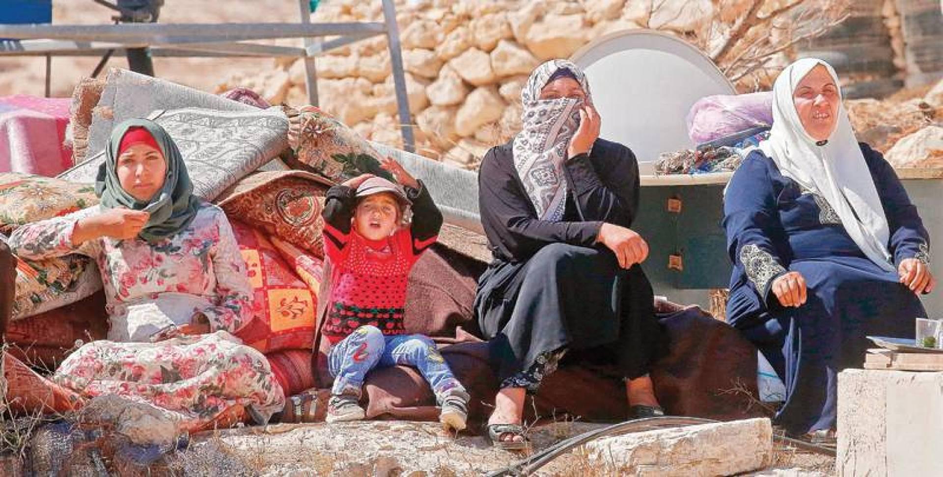 فلسطينيات يجلسن بينما تقوم قوات الاحتلال بهدم منازل متنقلة بُنيت بتمويل من الاتحاد الأوروبي في قرية بالقرب من الخليل في الضفة الغربية المحتلة | ا ف ب