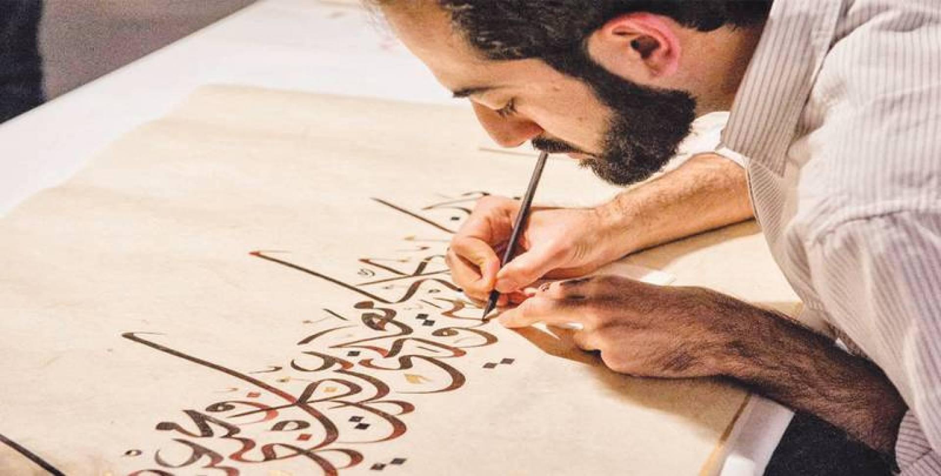 المعراج عاكفاً على إحدى لوحاته الخطية