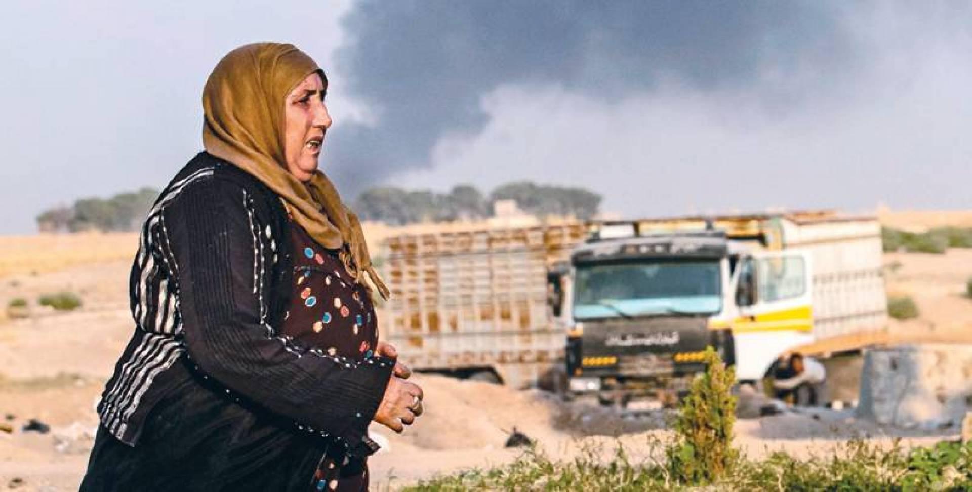 امرأة كردية في رأس العين وخلفها الدخان جراء القصف التركي | ا ف ب