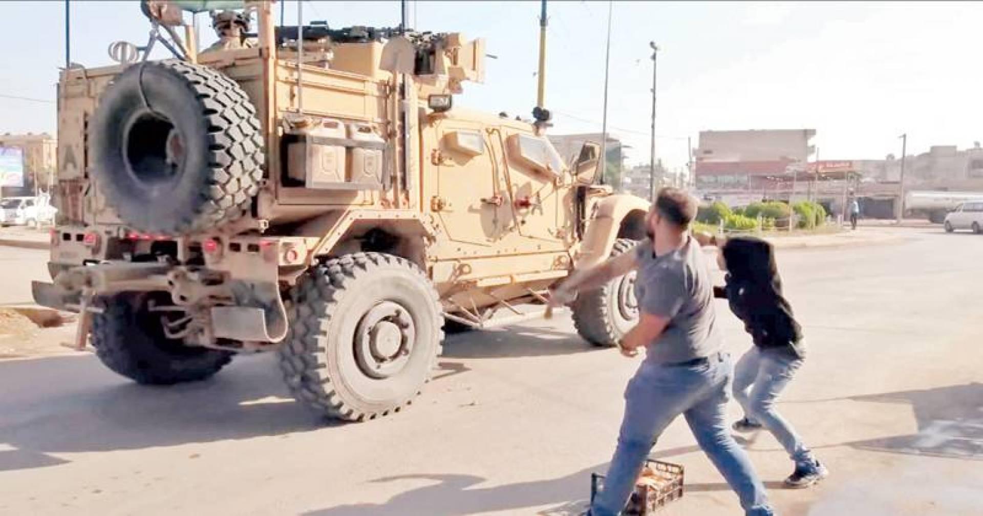 شابان يقذفان بالبطاطا مركبة عسكرية أميركية في مدينة القامشلي بالحسكة احتجاجاً على انسحاب قوات الولايات المتحدة من مناطق الأكراد | أ.ب