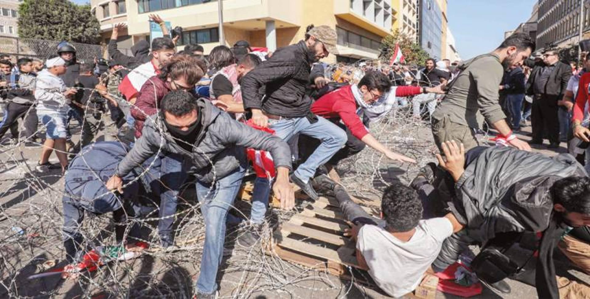 متظاهرون يحاولون عبور السياج الشائك للوصول إلى البرلمان أمس | أ.ف.ب