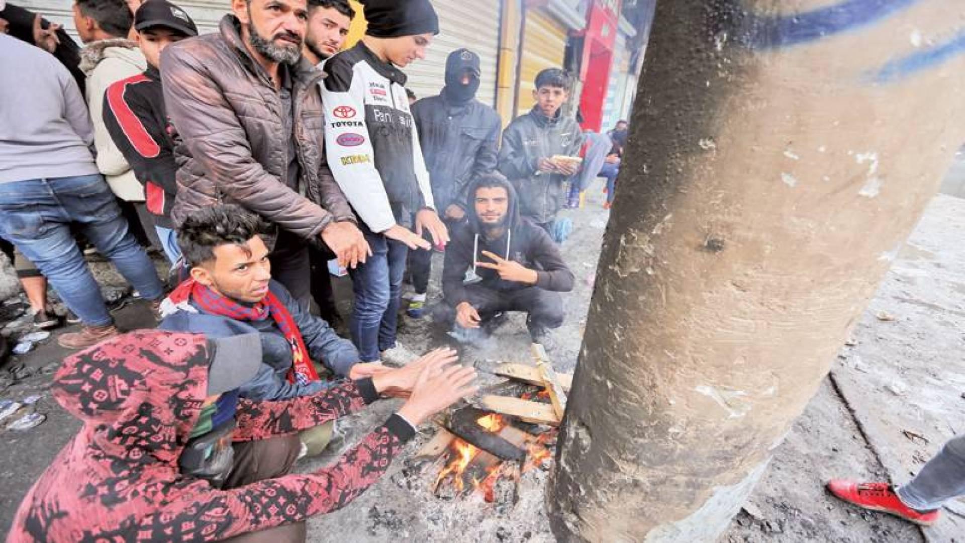 متظاهرون يتدفَّؤُون في شارع الرشيد بالعاصمة بغداد أمس | أ.ف.ب