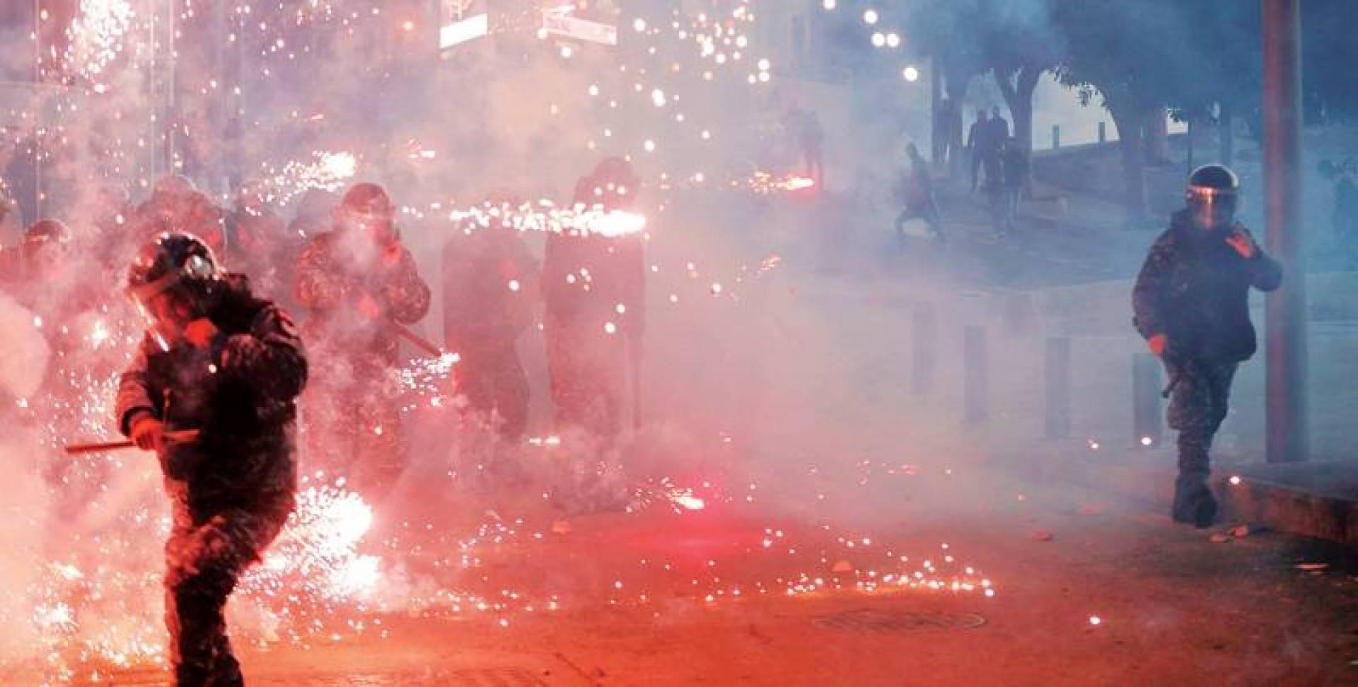 عناصر من قوى الامن يتفادون مفرقعات اطلقها مناصروا امل وحزب الله عليهم على جسر الرينغ وسط بيروت امس | ا ف ب