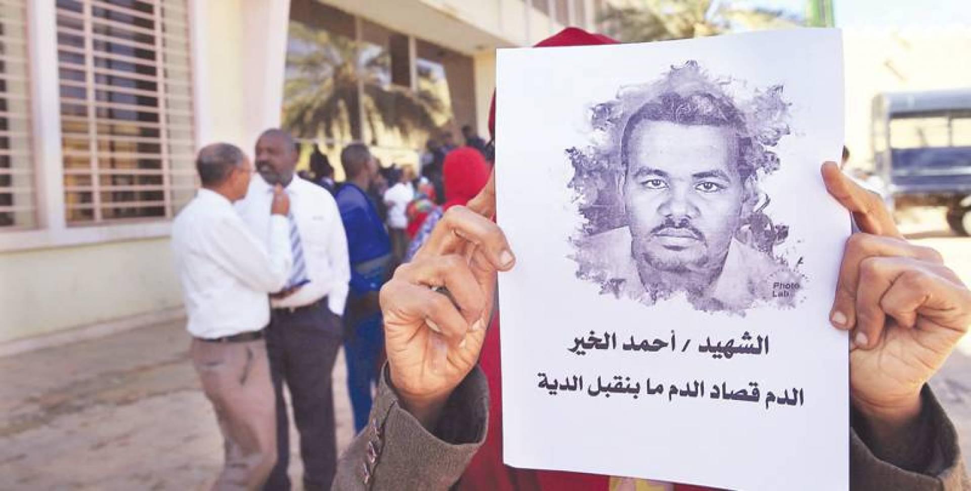 رجل يرفع صورة للمعلم أحمد الخير أمام محكمة في أم درمان | أ ف ب