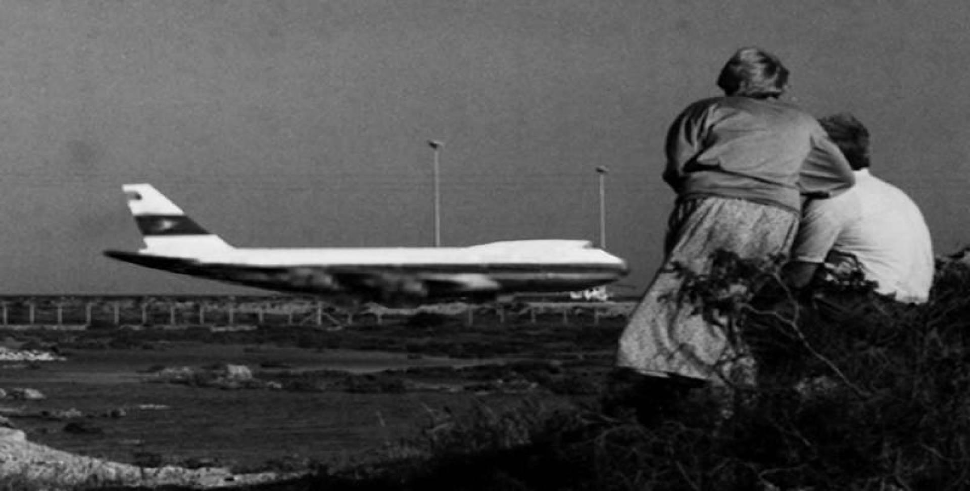 قبرصيان يتأملان طائرة الجابرية المختطفة على مهبط مطار لارنكا
