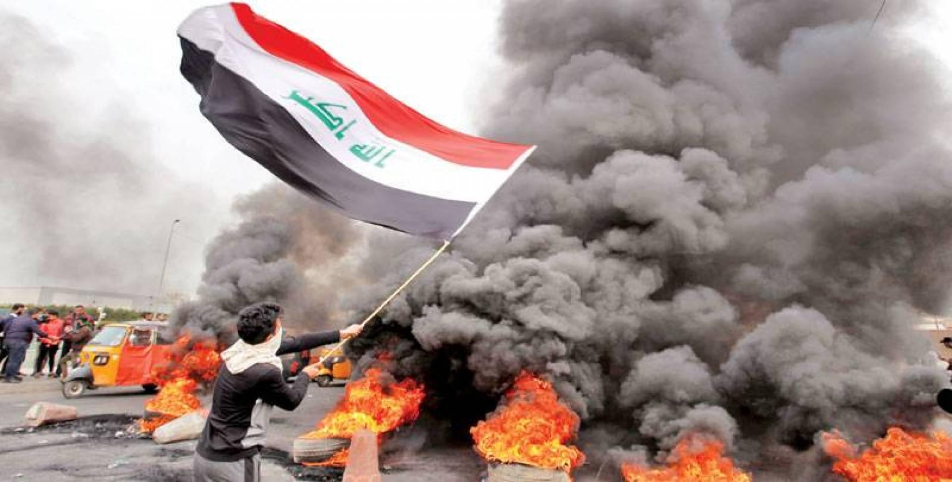 متظاهر رافعاً العلم العراقي قرب إطارات مشتعلة في بغداد أمس | أ ف ب