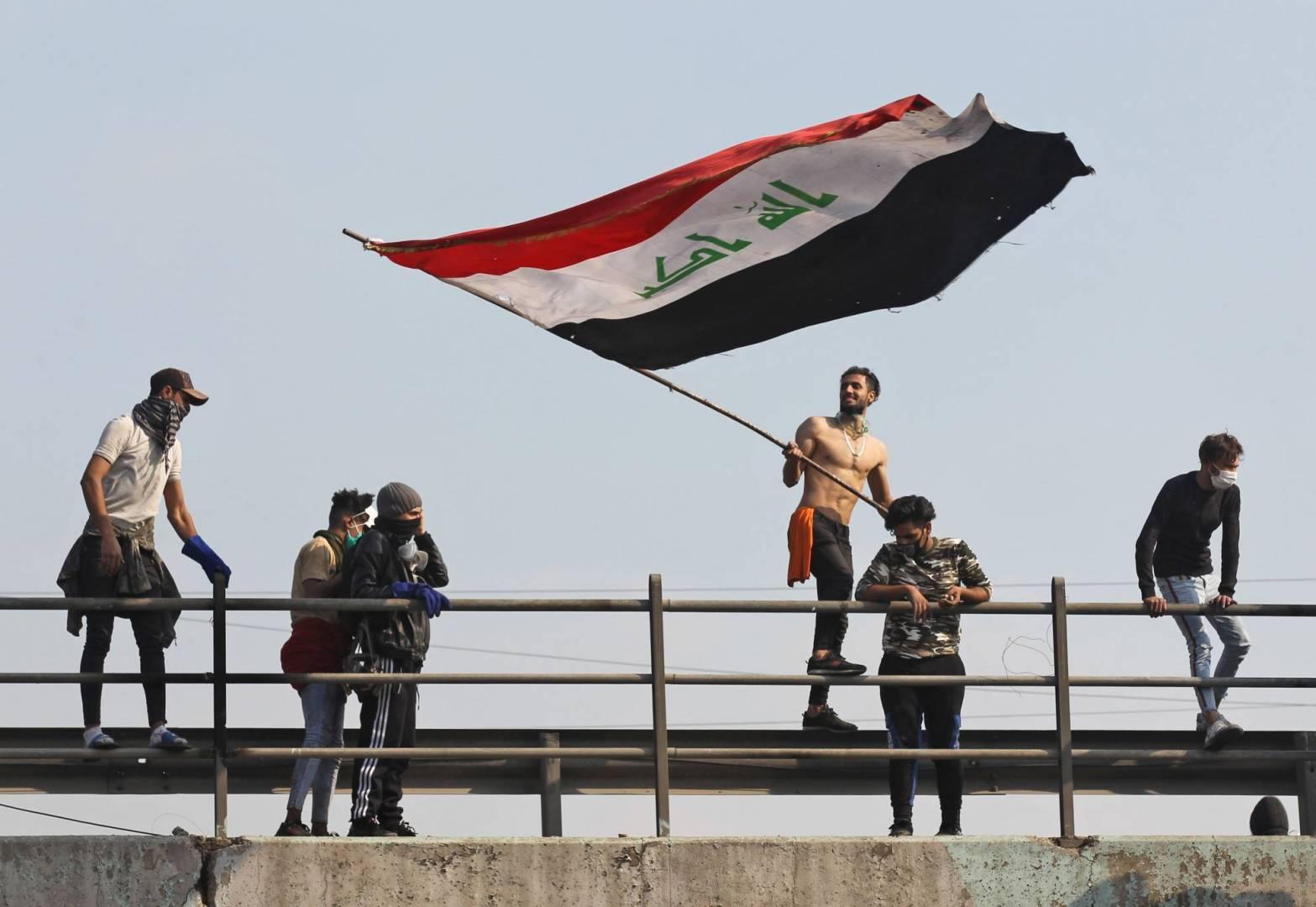 محتج عراقي يلوح بالعلم الوطني خلال مظاهرة مناهضة للحكومة على طريق محمد القاسم السريع