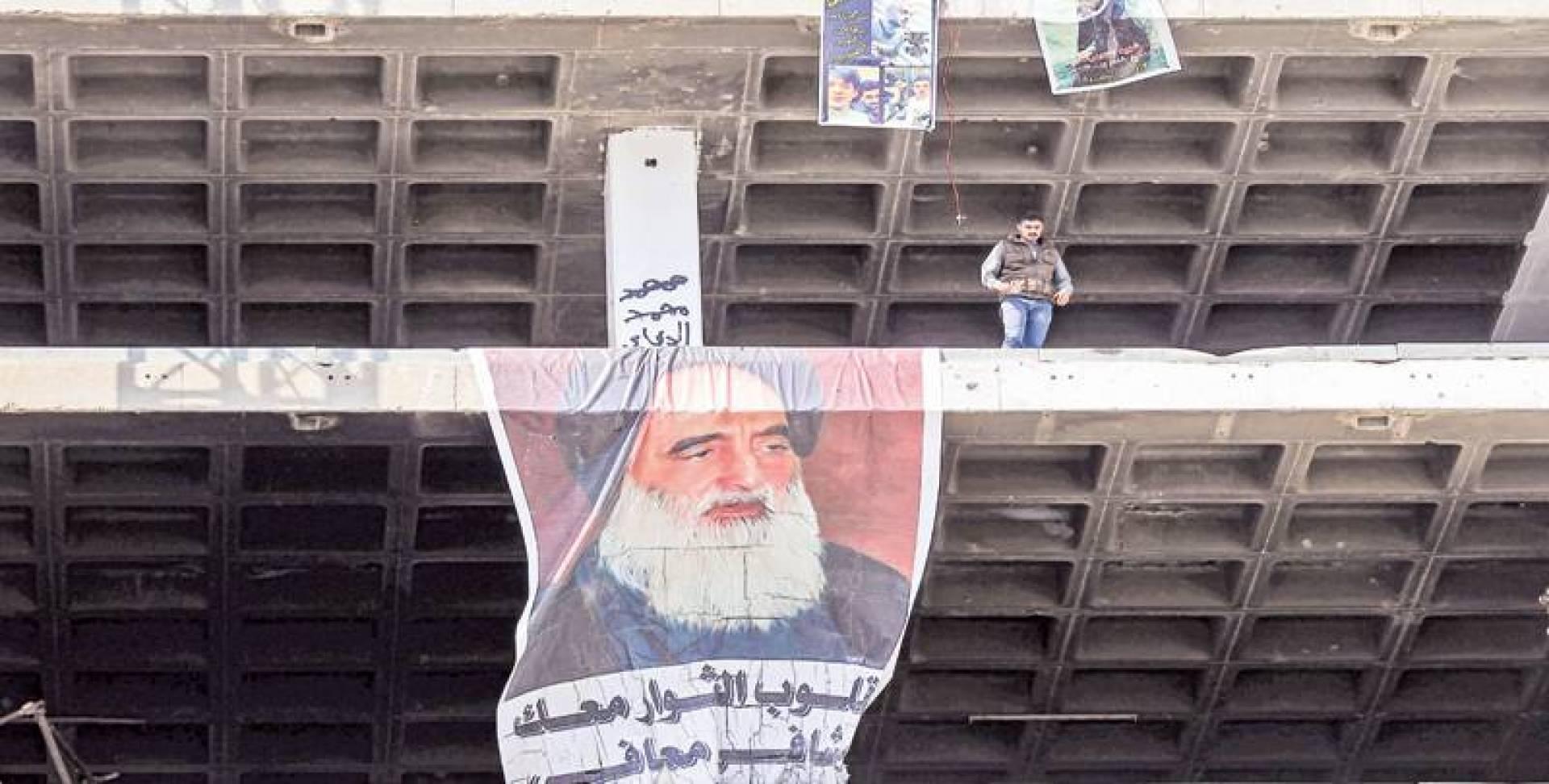 ملصق للسيستاني على مبنى يطل على تظاهرة مناهضة للحكومة في ميدان التحرير وسط بغداد أمس | رويترز