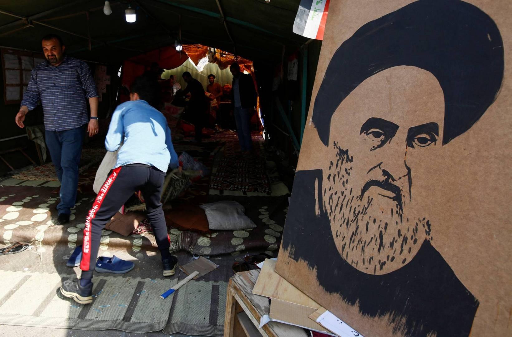 متظاهرون قرب ملصق للسيستاني خارج خيمة اعتصام في النجف   رويترز