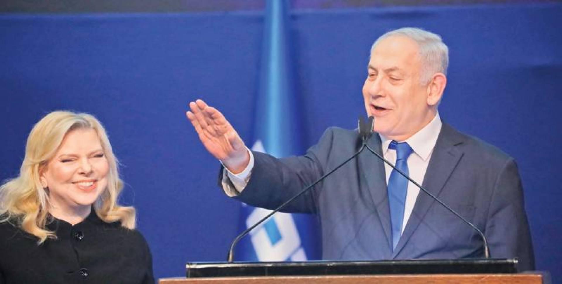 نتانياهو مع زوجته سارة مخاطباً مؤيديه بعد فوزه بالانتخابات بمقر حزبه في تل أبيب (أ.ب)