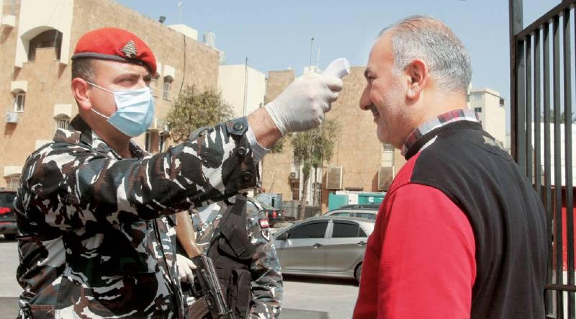 رجل أمن يفحص حرارة مراجع في السراي الحكومي بصيدا جنوبي لبنان (أ.ف.ب)