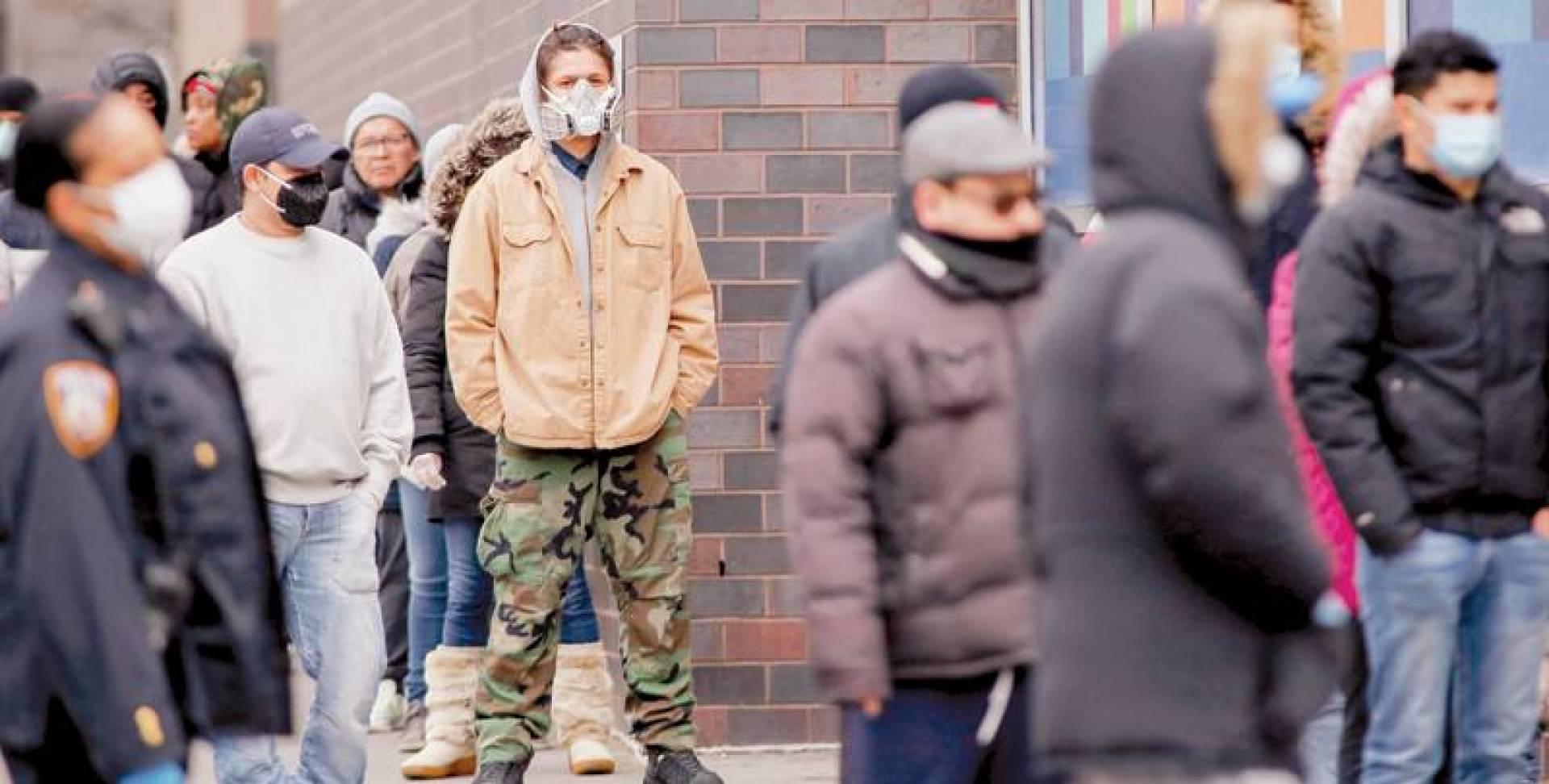 أشخاص ينتظرون دورهم لإجراء فحص «كورونا» خارج مستشفى «إلمهورست» في حي كوينز بمدينة نيويورك (رويترز)