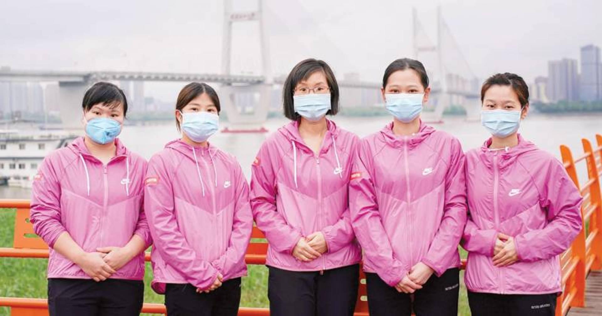 طبيبات يلتقطن صورة جماعية بعد وصولهن من غوانغدونغ إلى ووهان أمس (رويترز)