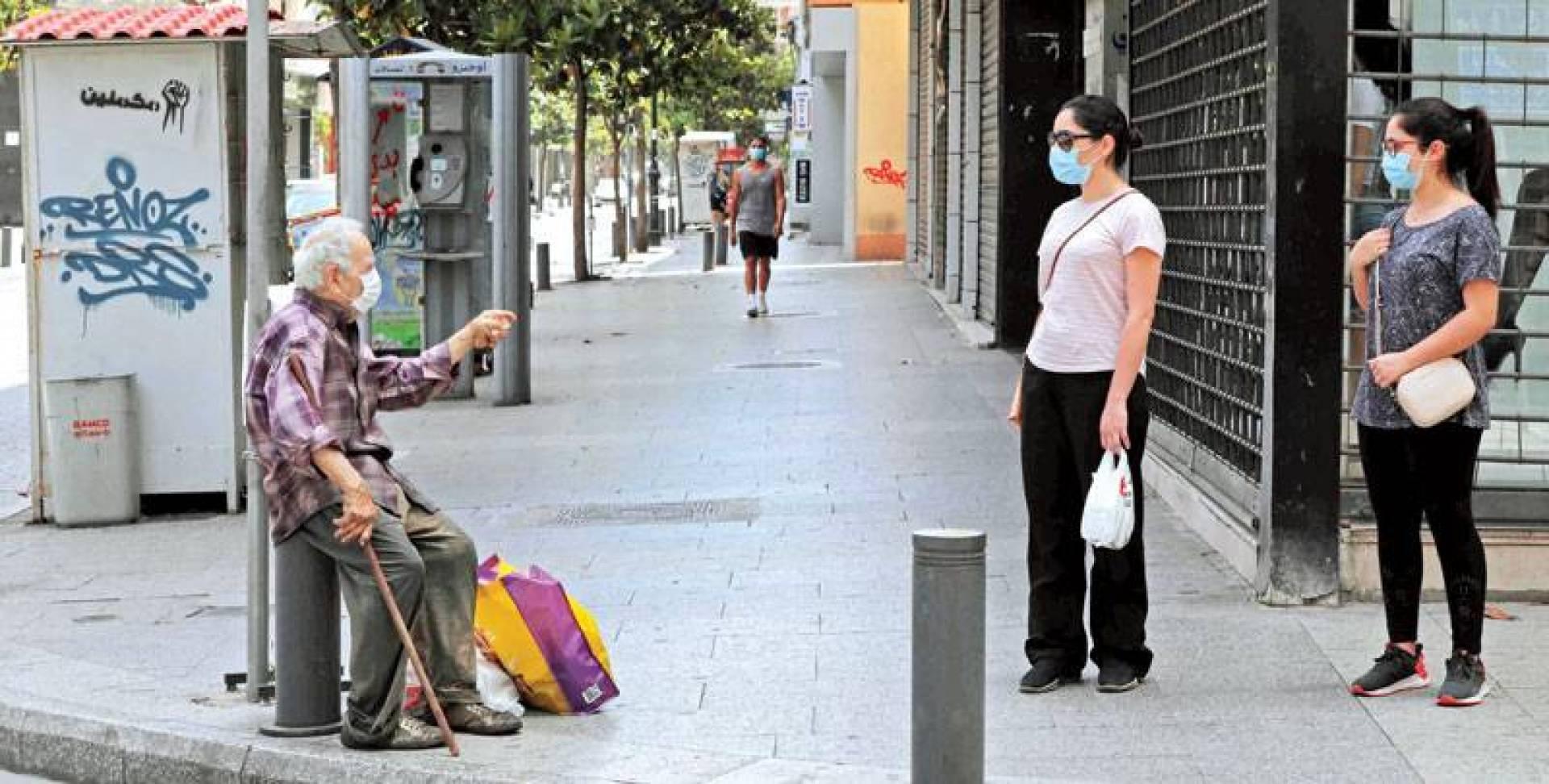 عجوز مرتدياً كماماً يلتمس صدقة في شارع الحمرا وسط بيروت (أ.ف.ب)