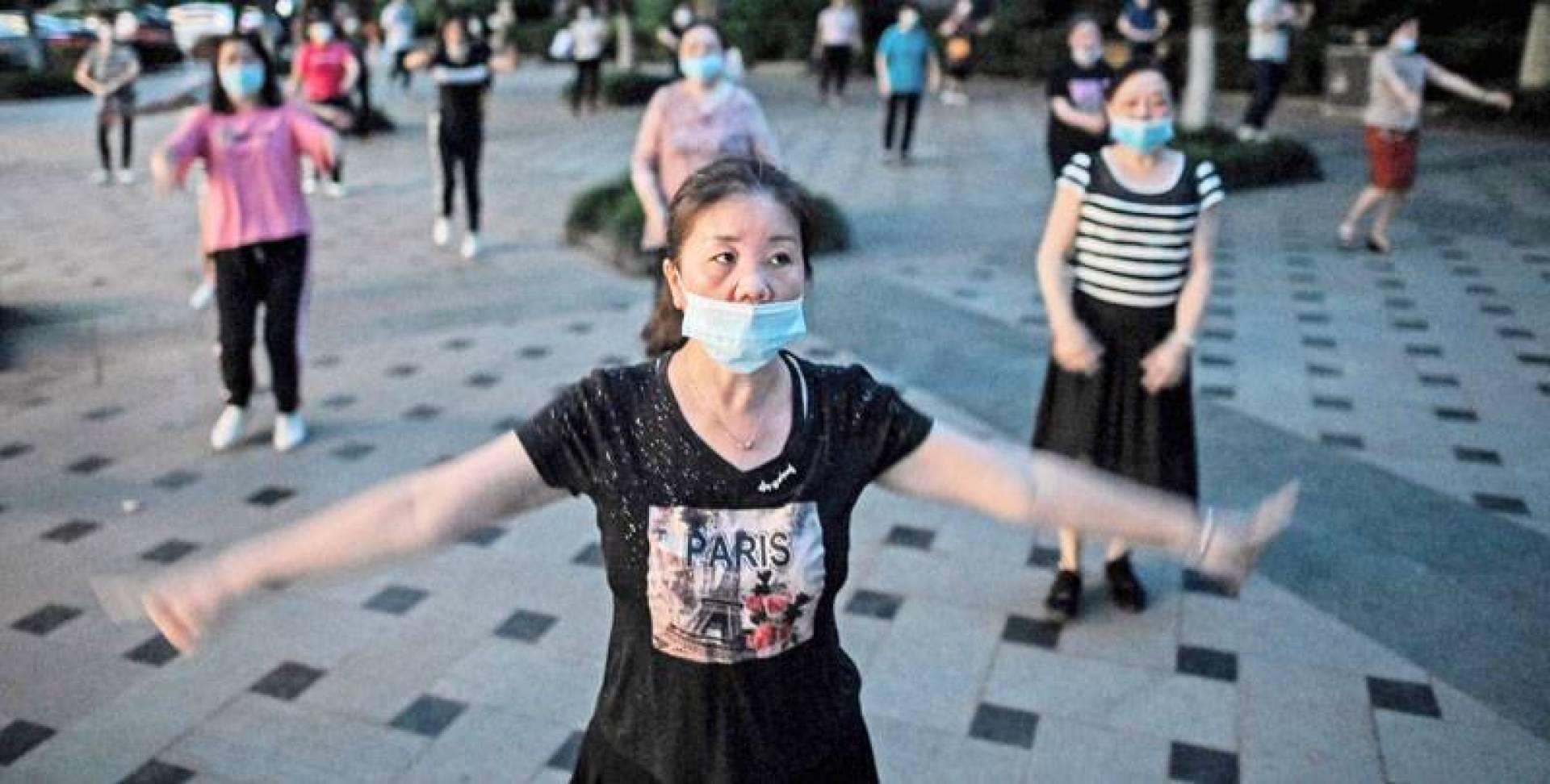 نساء يؤدين رقصة في حديقة بووهان بعد إعلان الصين الانتصارعلى «كورونا» (أ ف ب)