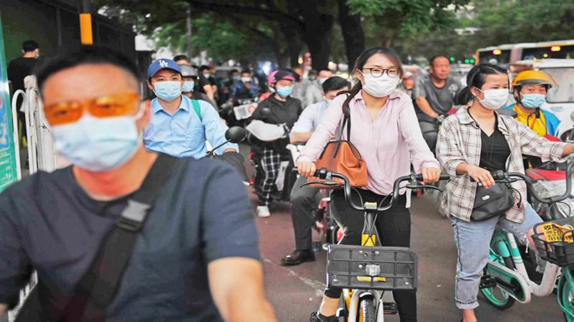 أشخاص بكمامات منتظرين عبور تقاطع مزدحم في بكين أمس (أ.ف.ب)