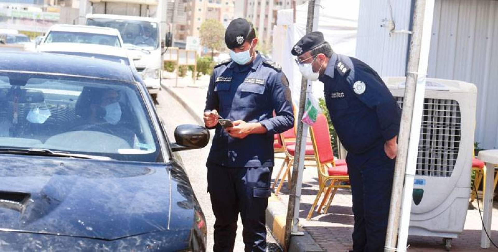 النقيب صلاح الظفيري ورجل الأمن خالد فيصل العنزي خلال التدقيق على التصاريح (تصوير: حسني هلال)