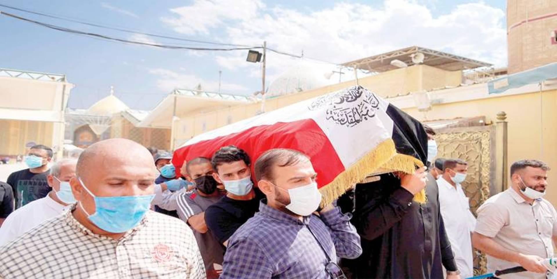 مشيعون يحملون نعش الهاشمي خلال جنازته في مدينة النجف أمس (رويترز)