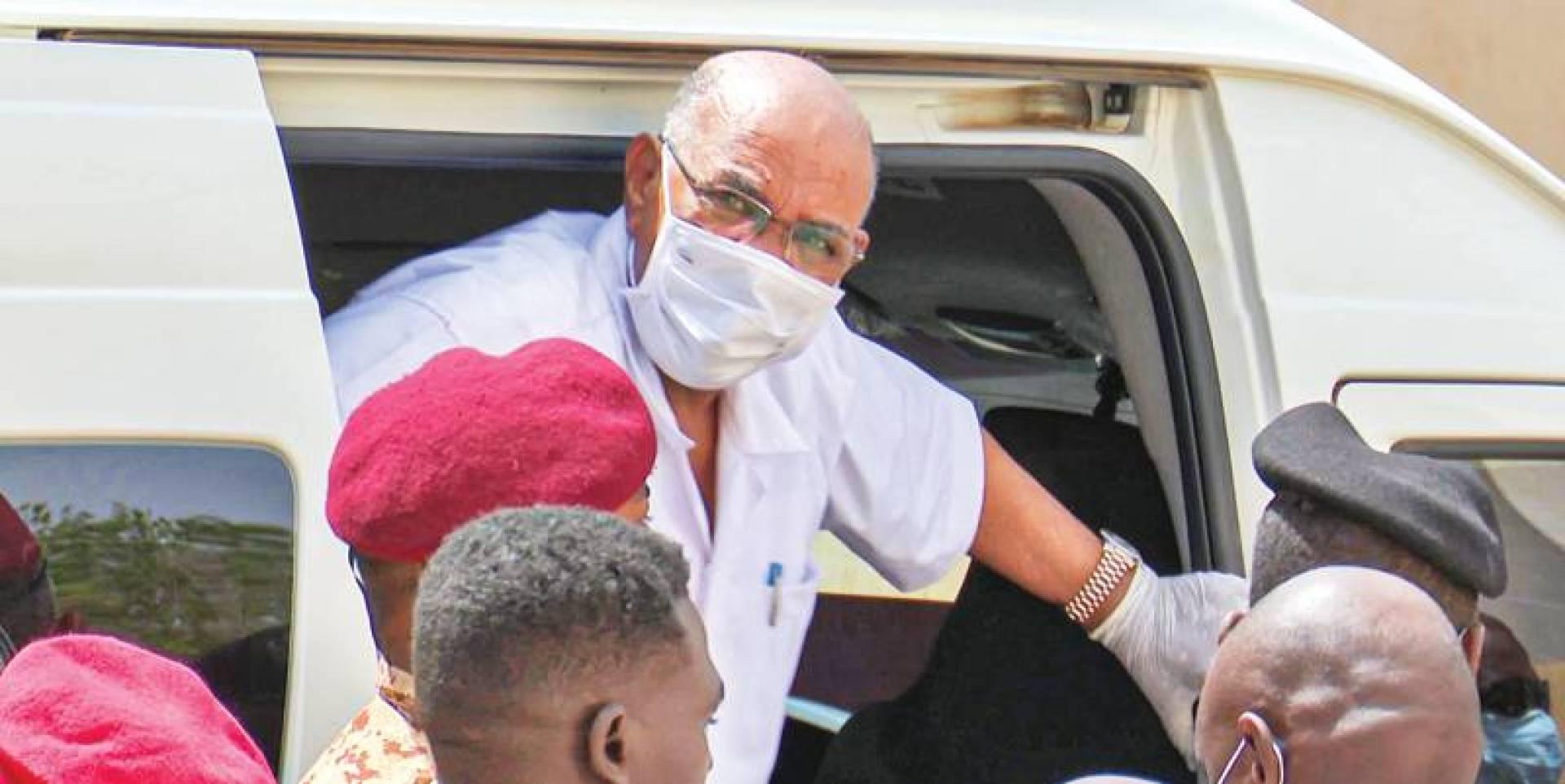عمر البشير لدى نزوله من سيارة نقل السجناء إلى المحكمة في الخرطوم (أ ف ب)