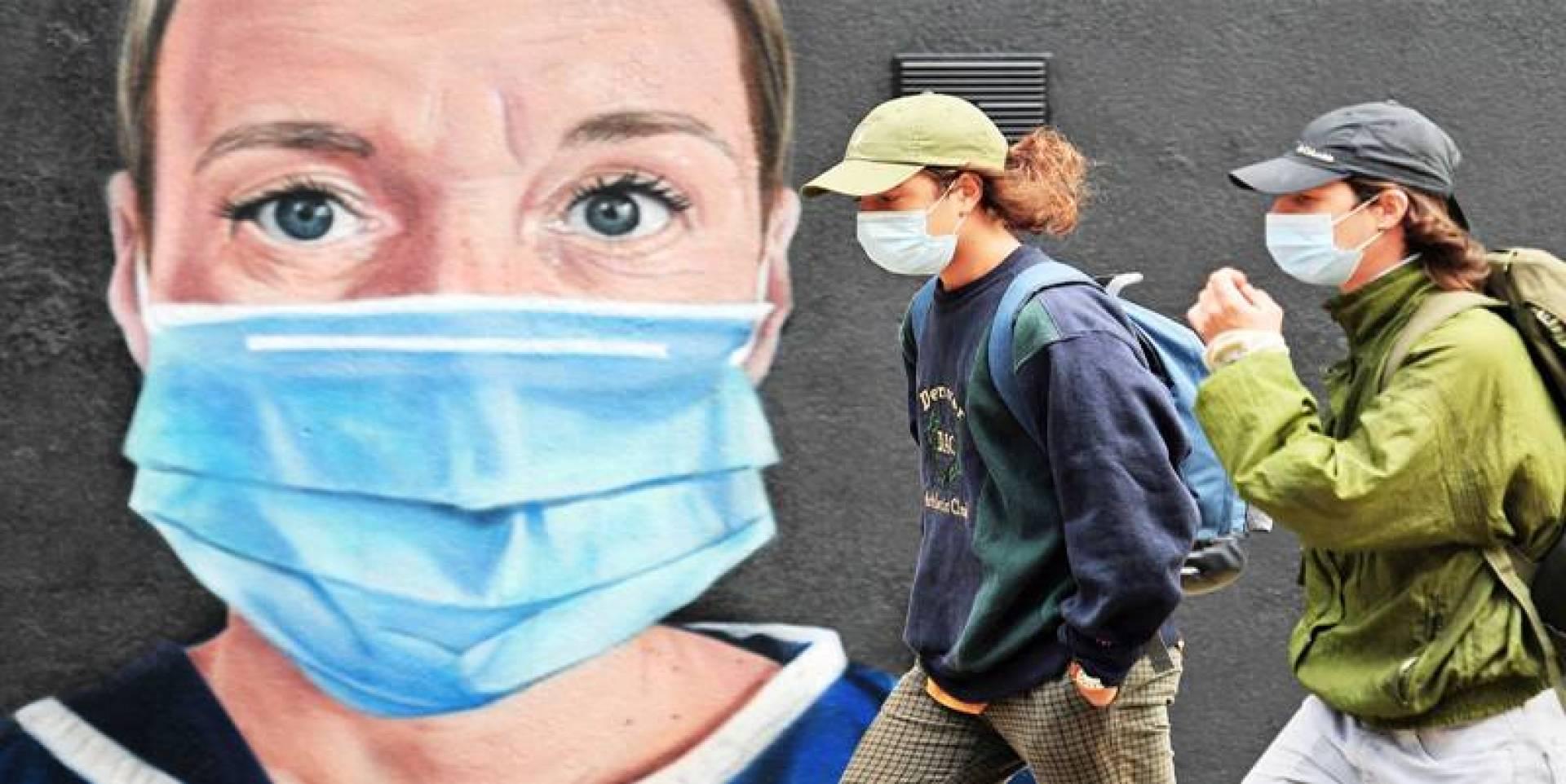 بريطانيان يمشيان قرب جدارية لممرضة تضع كماماً في مانشستر شمال غربي إنكلترا (أ.ف.ب)