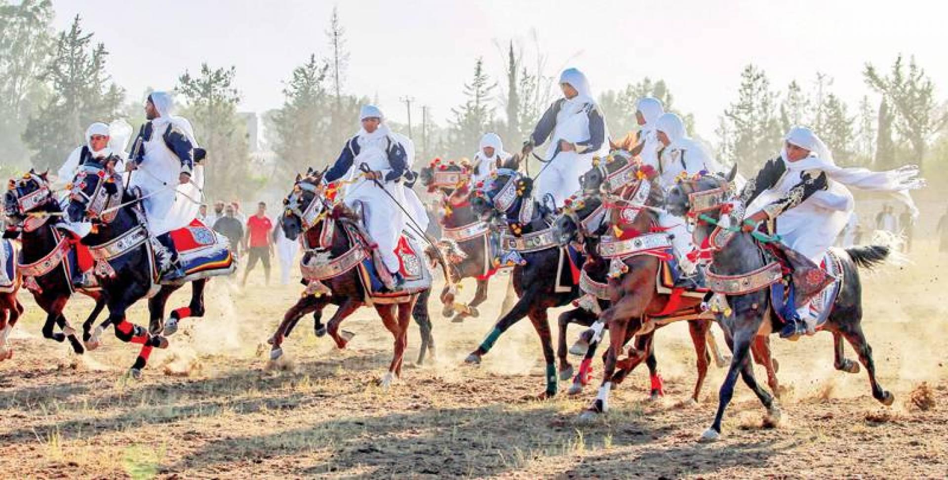 ليبيون بأزياء تقليدية على الخيول خلال مهرجان الفروسية الشعبي قرب طرابلس أمس (أ ف ب)