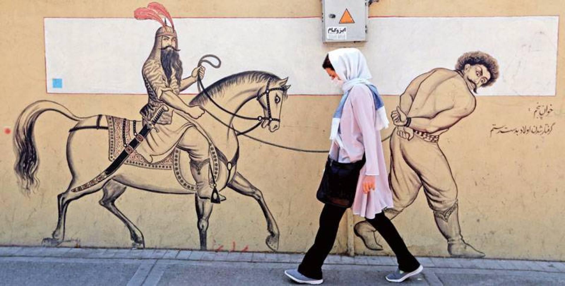 إيرانية ترتدي كماماً قرب جدارية تصور البطل الفارسي الأسطوري رستم  راكباً حصانه خلف سجين مكبل اليدين في طهران أمس  (أ.ف.ب)