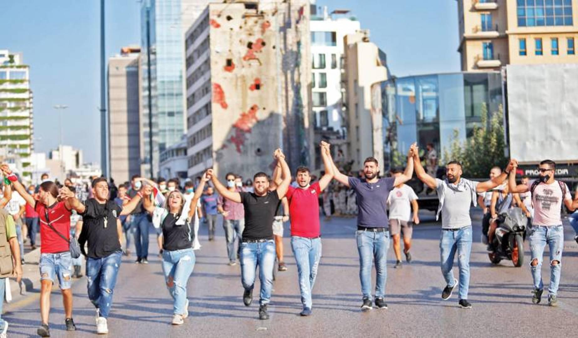 لبنانيون يشبكون أياديهم أثناء مسيرة  في بيروت بمناسبة مرور عام على الاحتجاجات  التي عرفت بـ«ثورة 17 اكتوبر» (أ ف ب)