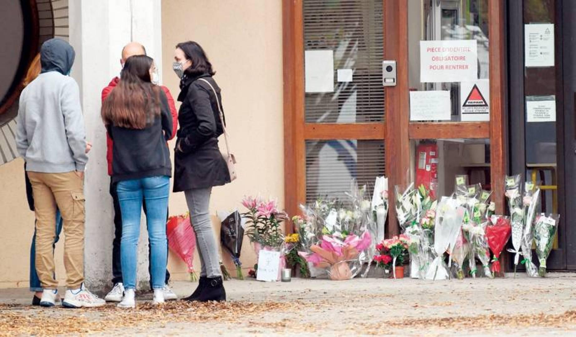 تلاميذ يتحدثون بجانب زهور عند مدخل المدرسة في كونفلان بعد قتل المدرّس (أ ف ب)