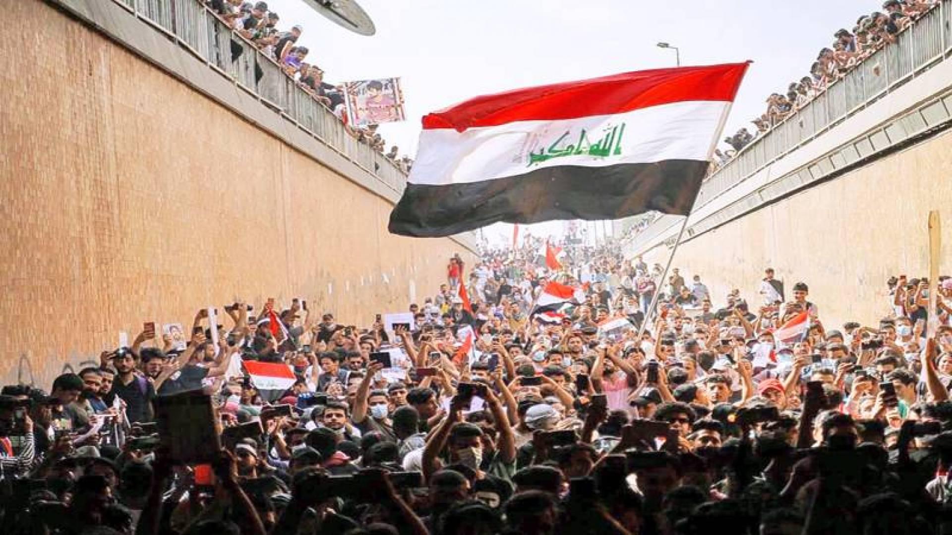 المتظاهرون رافعين الأعلام العراقية خلال تجمع في بغداد أمس