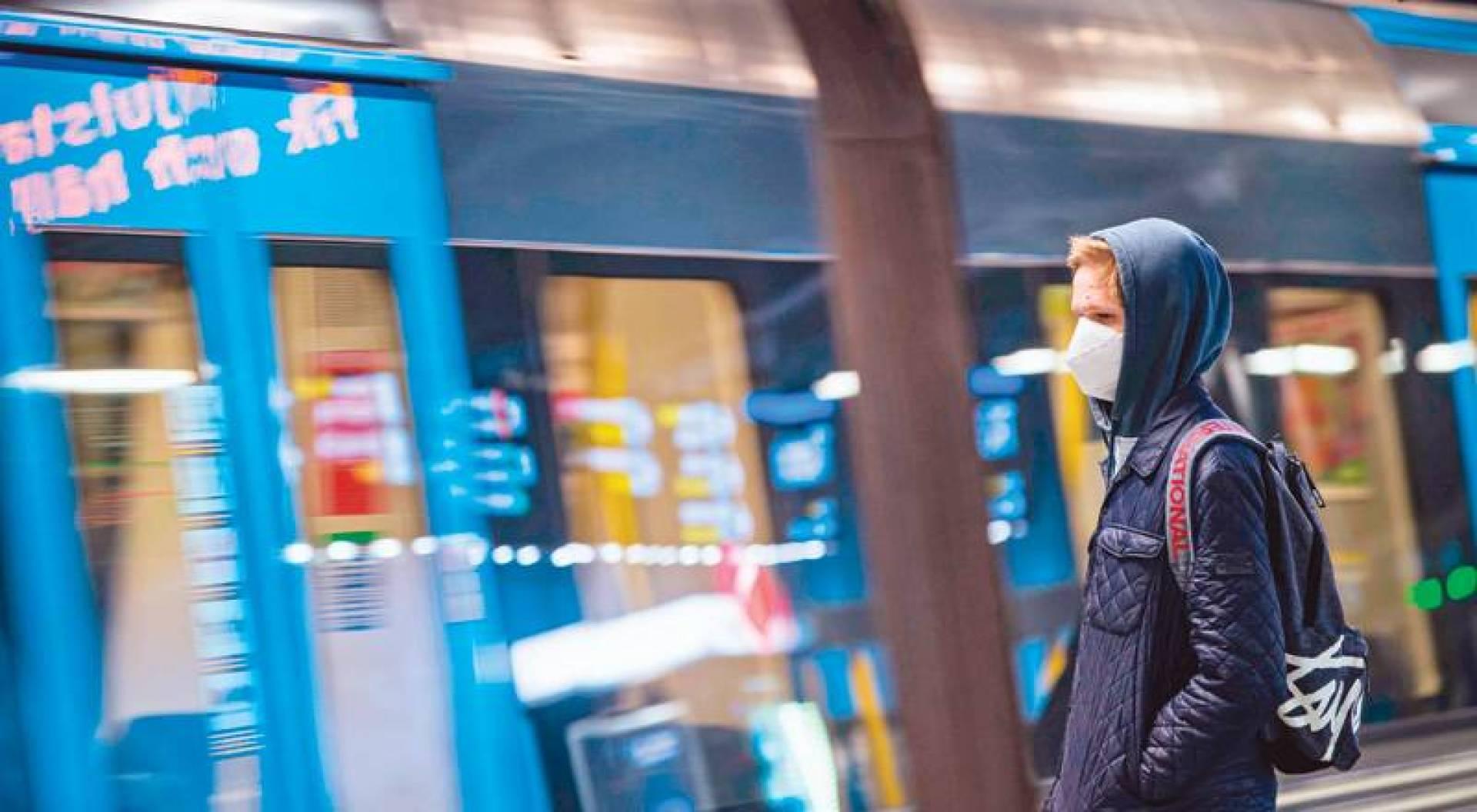 مسافر مرتدياً كماماً ينتظر المترو بمحطة استوكهولم